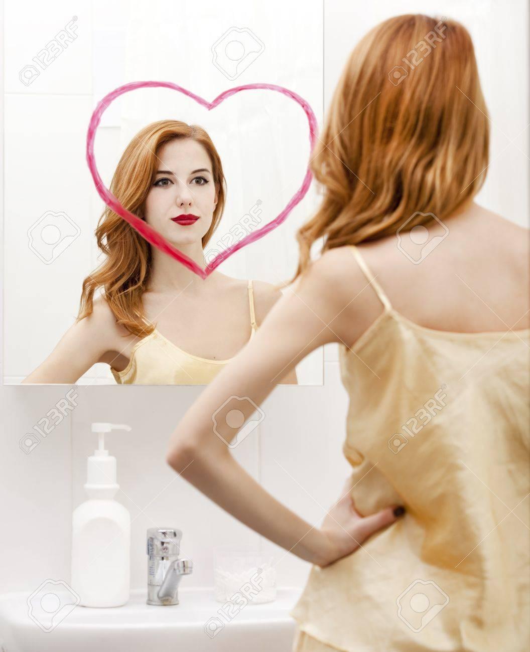 Redhead girl near mirror with heart it in bathroom. Stock Photo - 16824857
