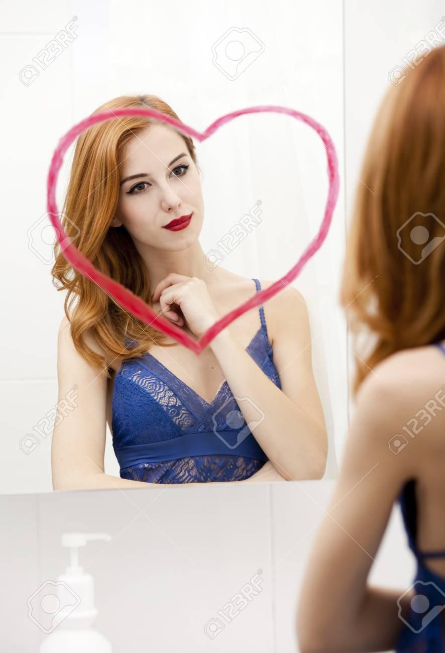 Redhead girl near mirror with heart it in bathroom. Stock Photo - 16824805