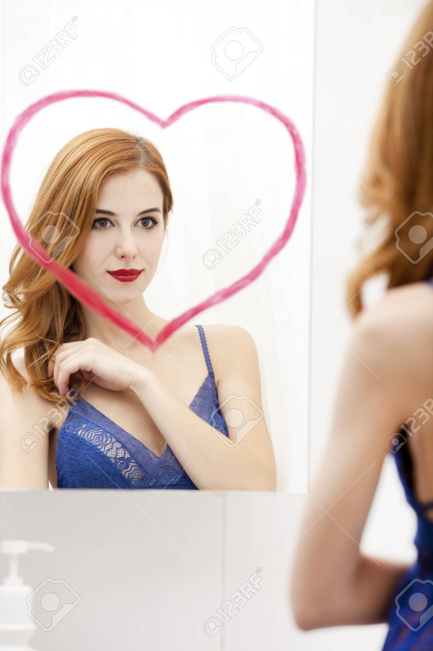 Redhead girl near mirror with heart it in bathroom. Stock Photo - 16824779