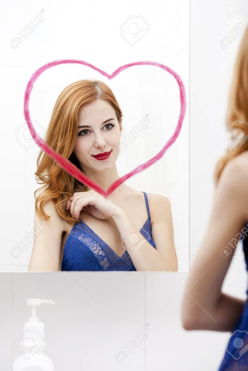 Redhead girl near mirror with heart it in bathroom. Stock Photo - 16824861