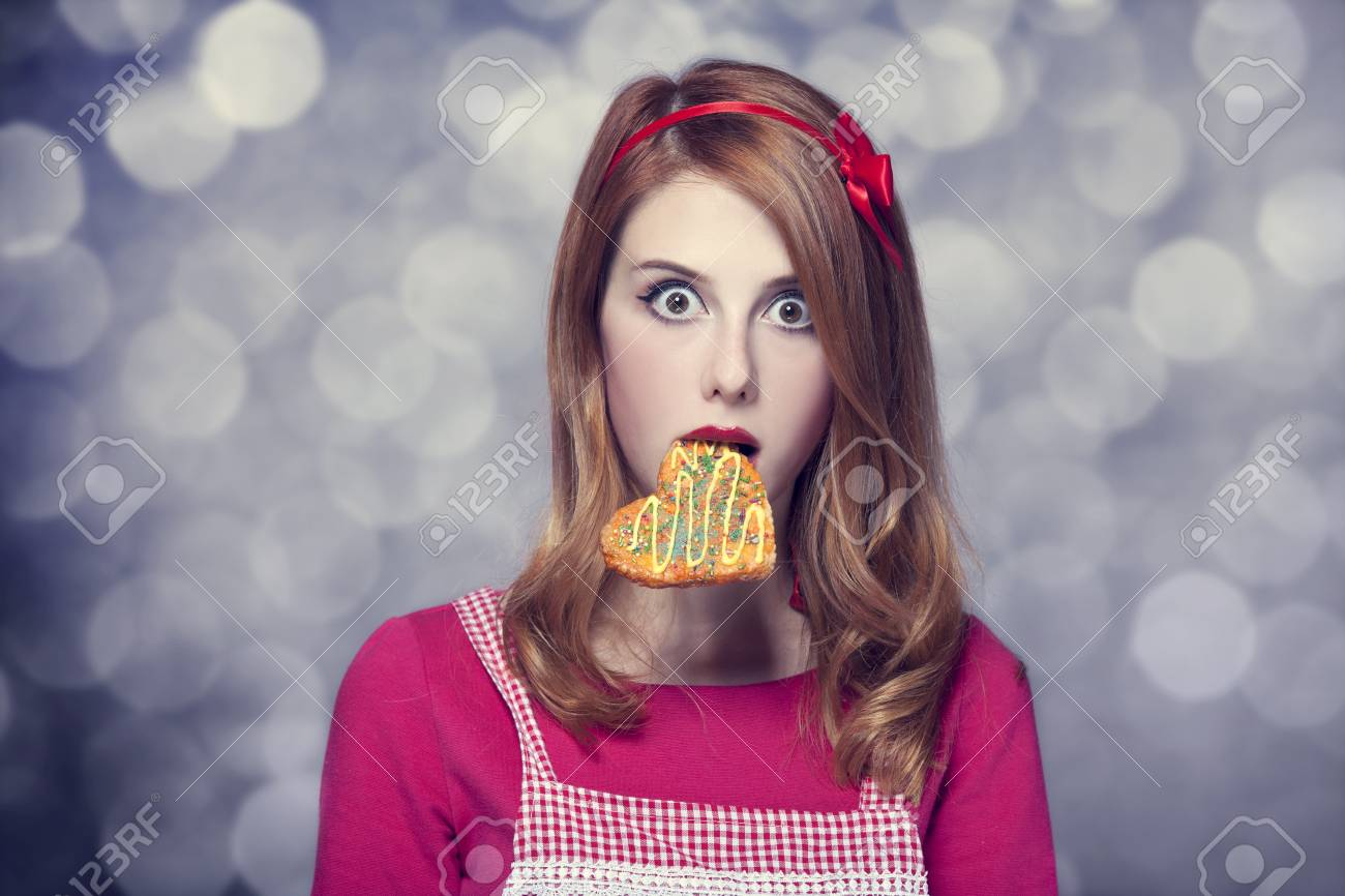 Redhead women with cookie Stock Photo - 17602526