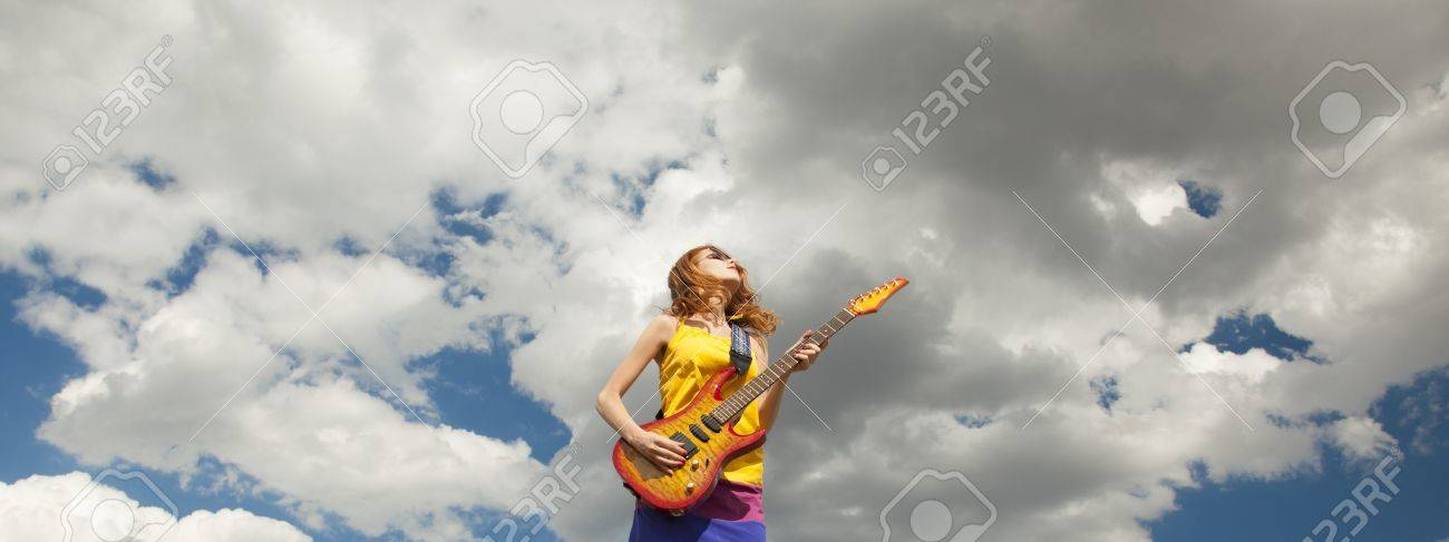 Redhead girl jumping with guitar at outdoor. Stock Photo - 17602518