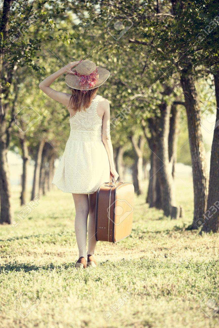 Redhead girl with suitcase at tree's alley. Stock Photo - 17602531