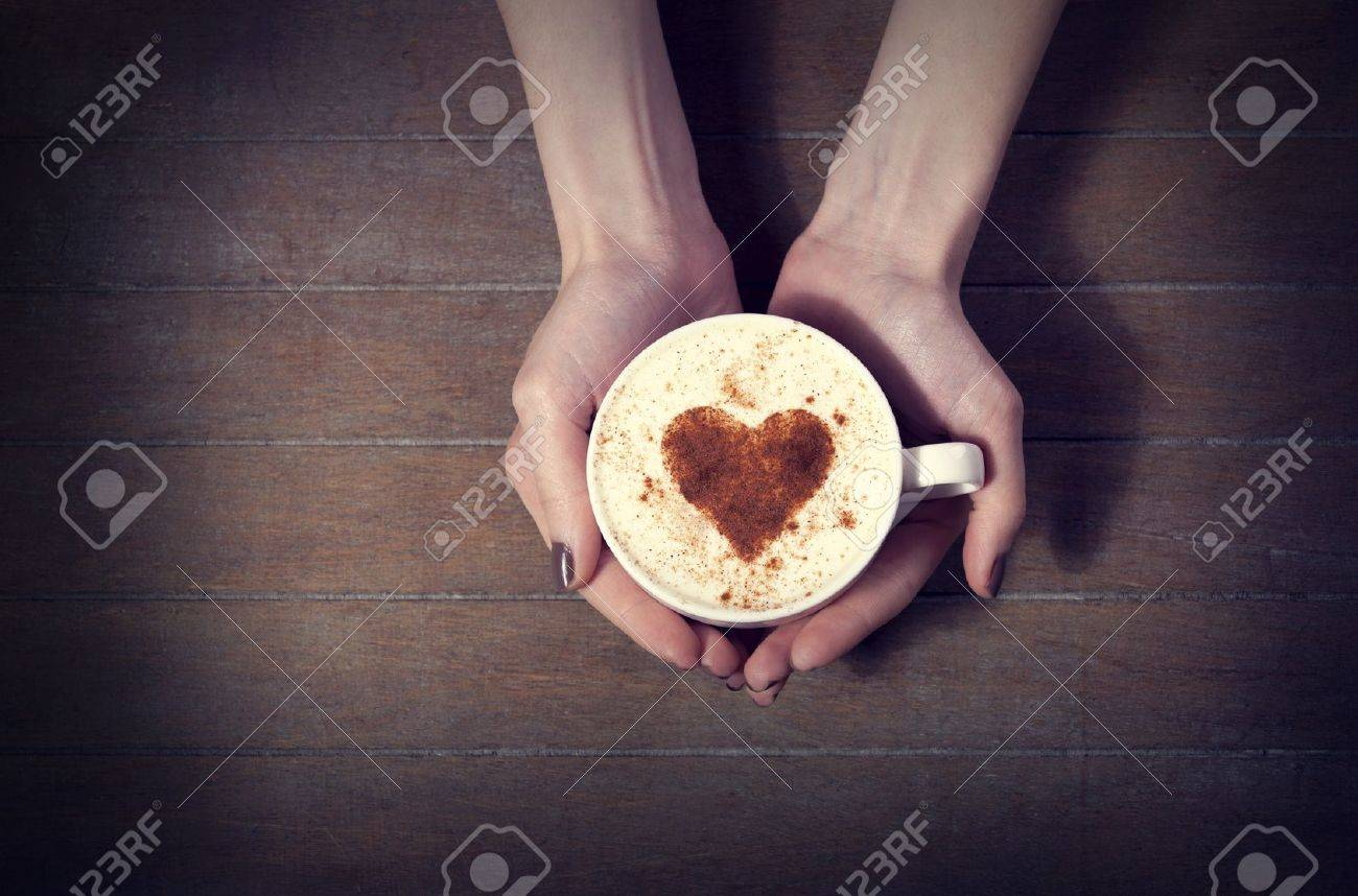 woman holding hot cup of coffee, with heart shape Stock Photo - 18031178