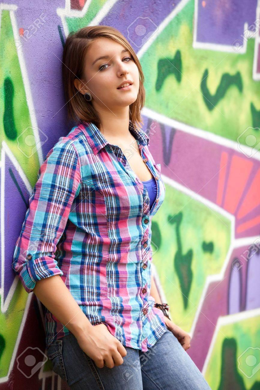 Style teen girl standing near graffiti wall. Stock Photo - 18342316