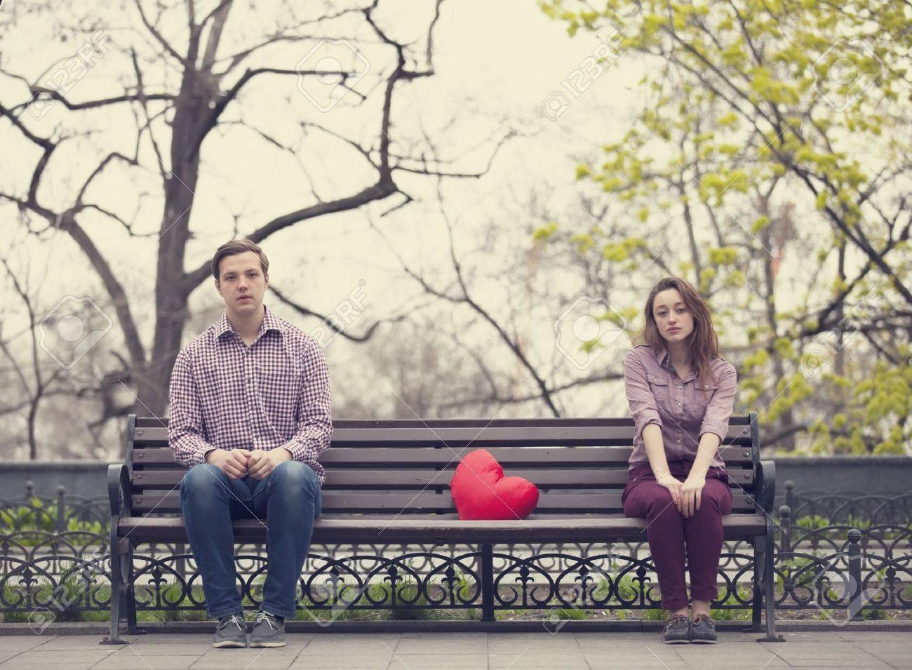 Sad teens sitting at the bench at the park Stock Photo - 19336977