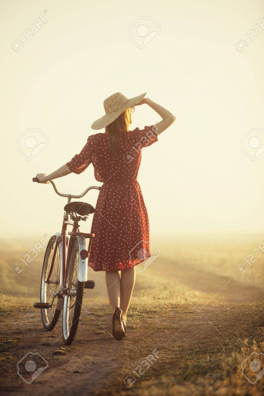 Girl on a bike in the countryside in sunrise time. Stock Photo - 19430889