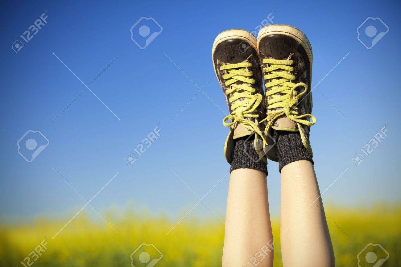 vintage sneakers resting on blue sky and rapseed field background Stock Photo - 19583512