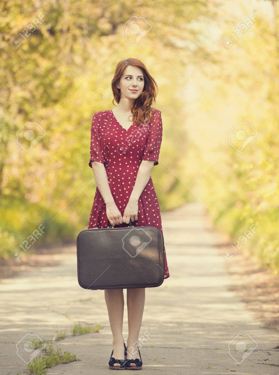 Redhead girl with suitcase at tree's alley. Stock Photo - 19583771