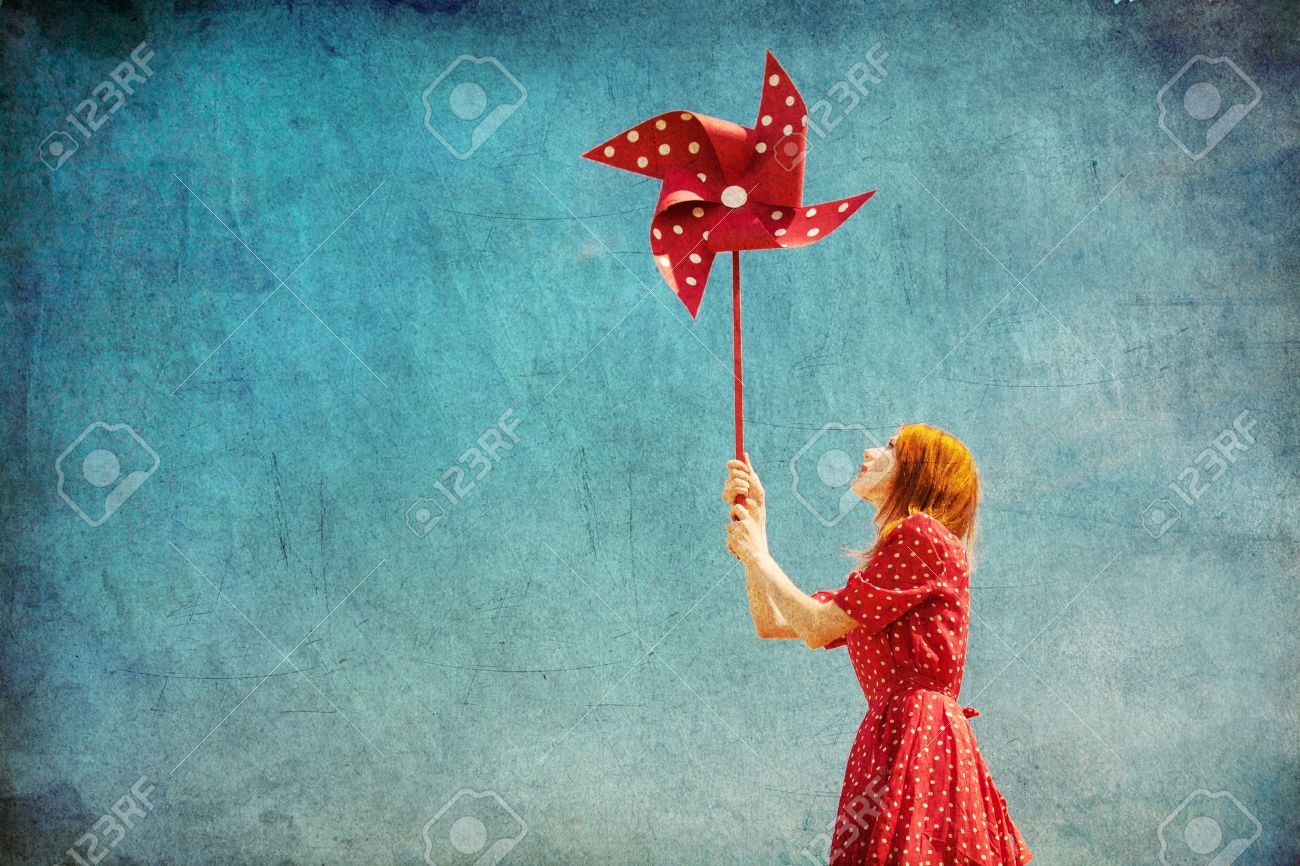 Girl with wind turbine at blue sky background. Stock Photo - 19915489