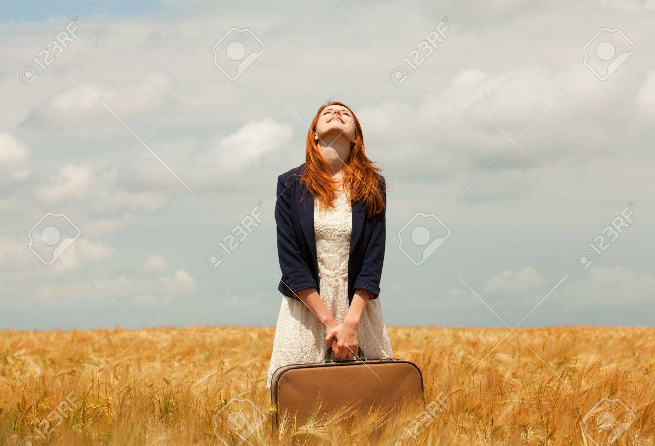 Redhead girl with suitcase at spring wheat field. Stock Photo - 20251400