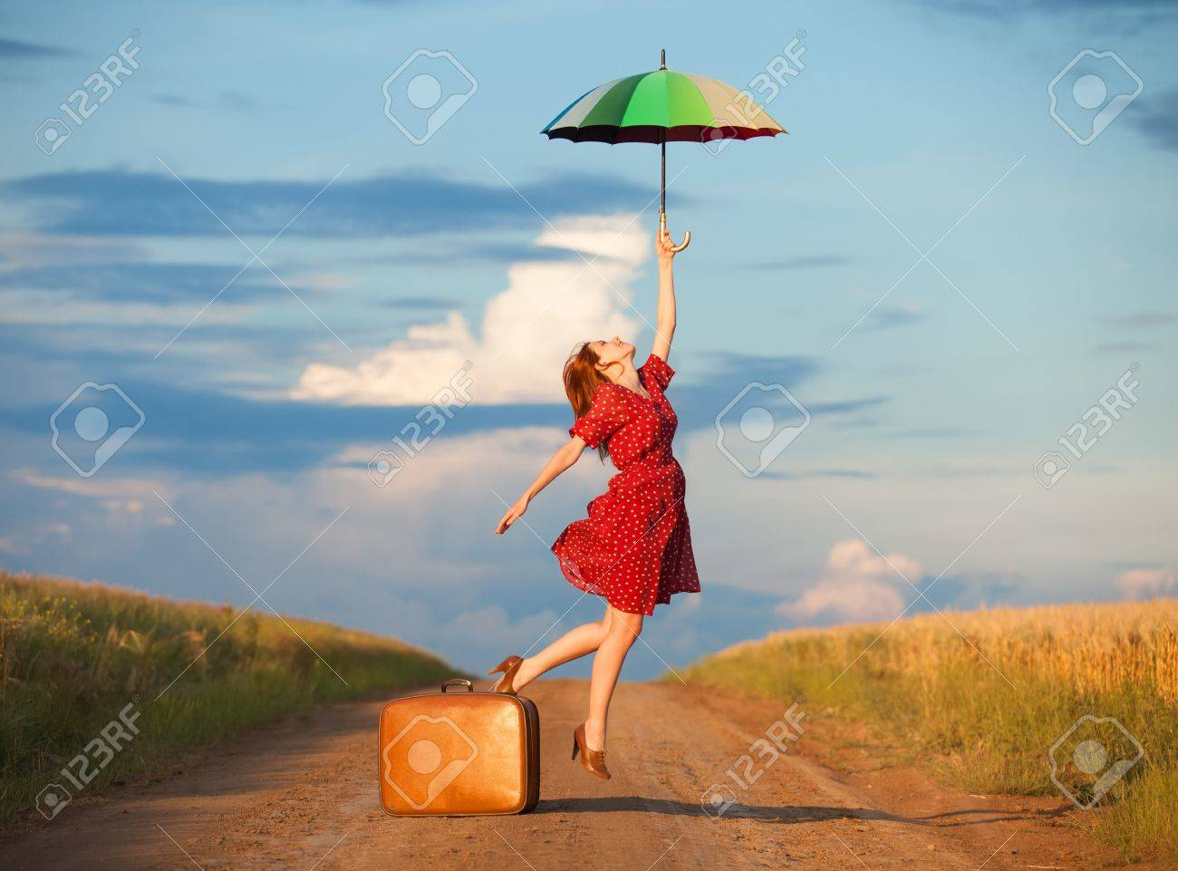 Redhead girl with umbrella and suitcase at outdoor Stock Photo - 20260942