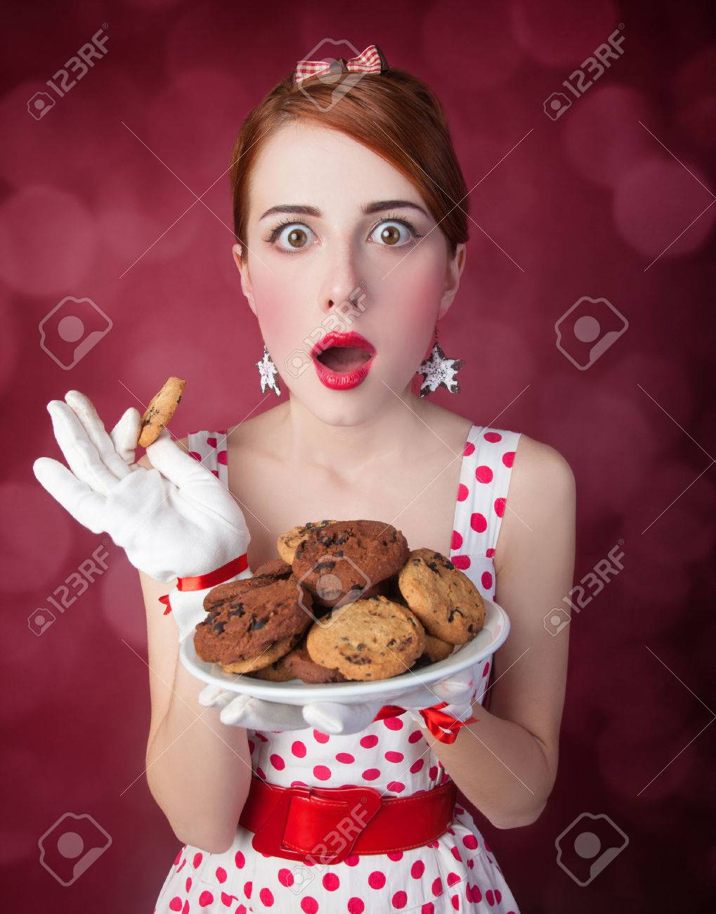 Beautiful redhead women with coockie. Photo in retro style with bokeh at background. Stock Photo - 23518814