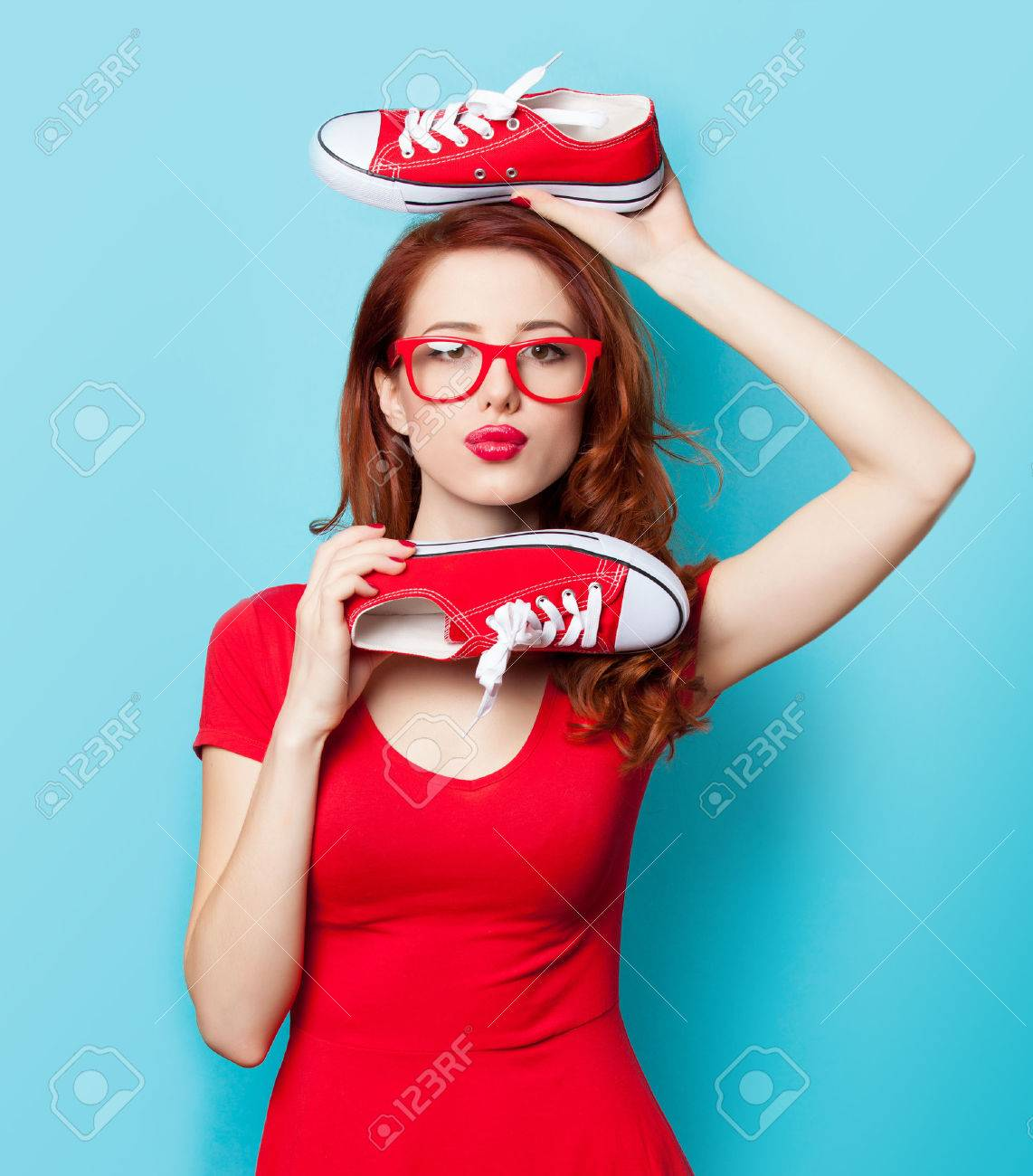 Surprised redhead girl in red dress with gumshoes on blue background. - 37324317