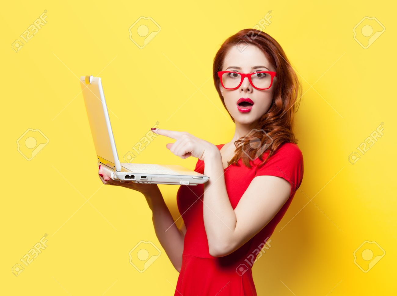 Surprised redhead girl with laptop on yellow background - 37324384