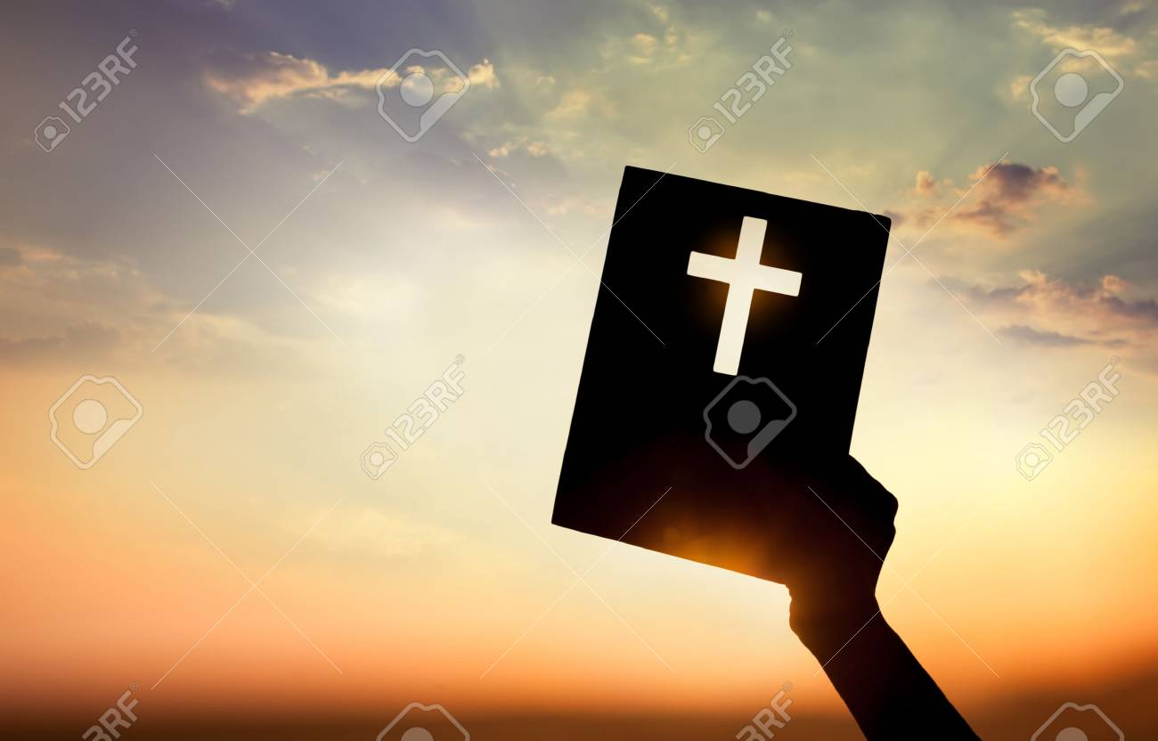 Hand holding book with cross on sunset background - 37470922