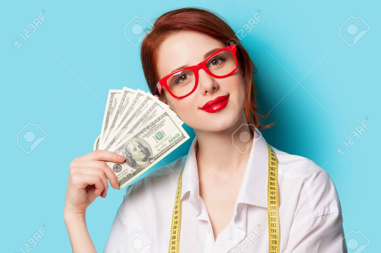 Portrait of redhead women in red glasses with money on blue background - 38322907