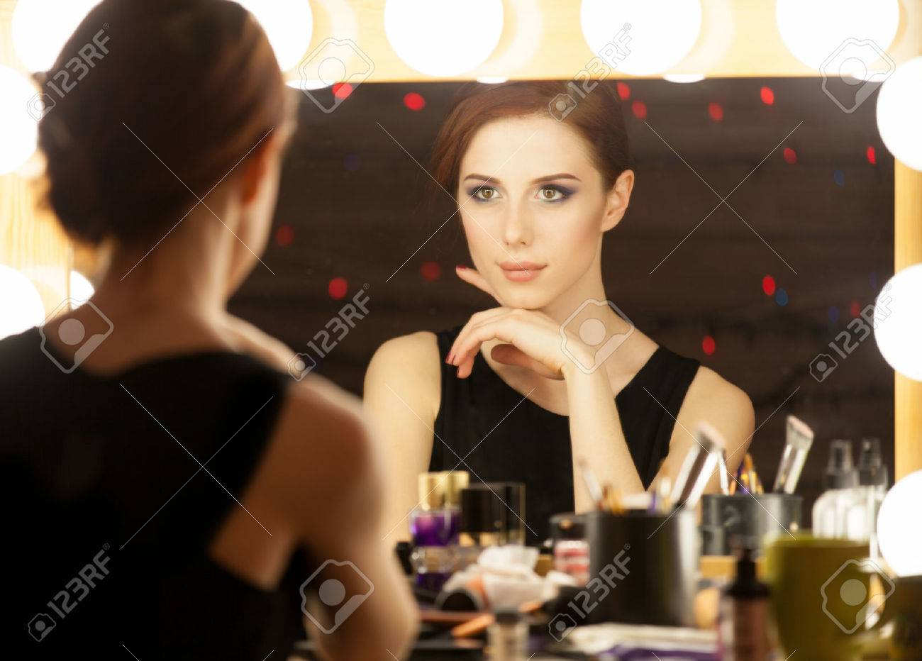 Portrait of a beautiful woman as applying makeup near a mirror. Photo in retro color style. - 39590985