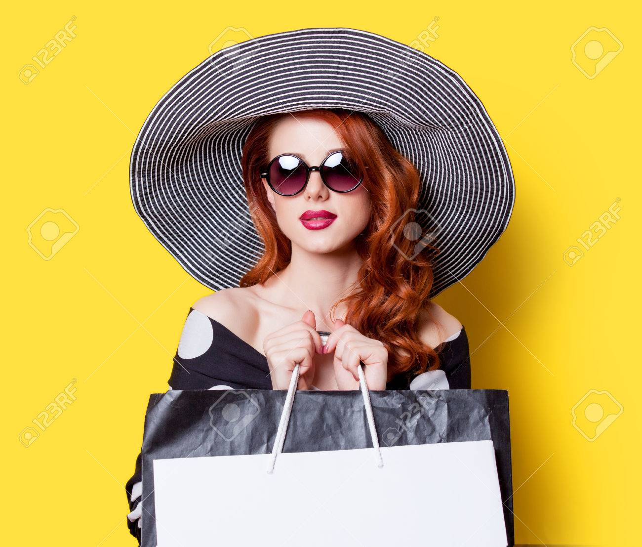 Redhead girl in black dress and hat with shopping bags on yellow background - 40455213