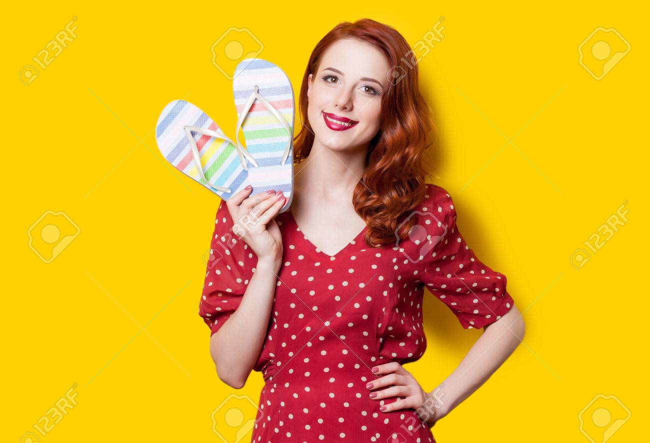 0e52a6b0588e Smiling redhead girl in red polka dot dress with flip flops on yellow  background. Stock