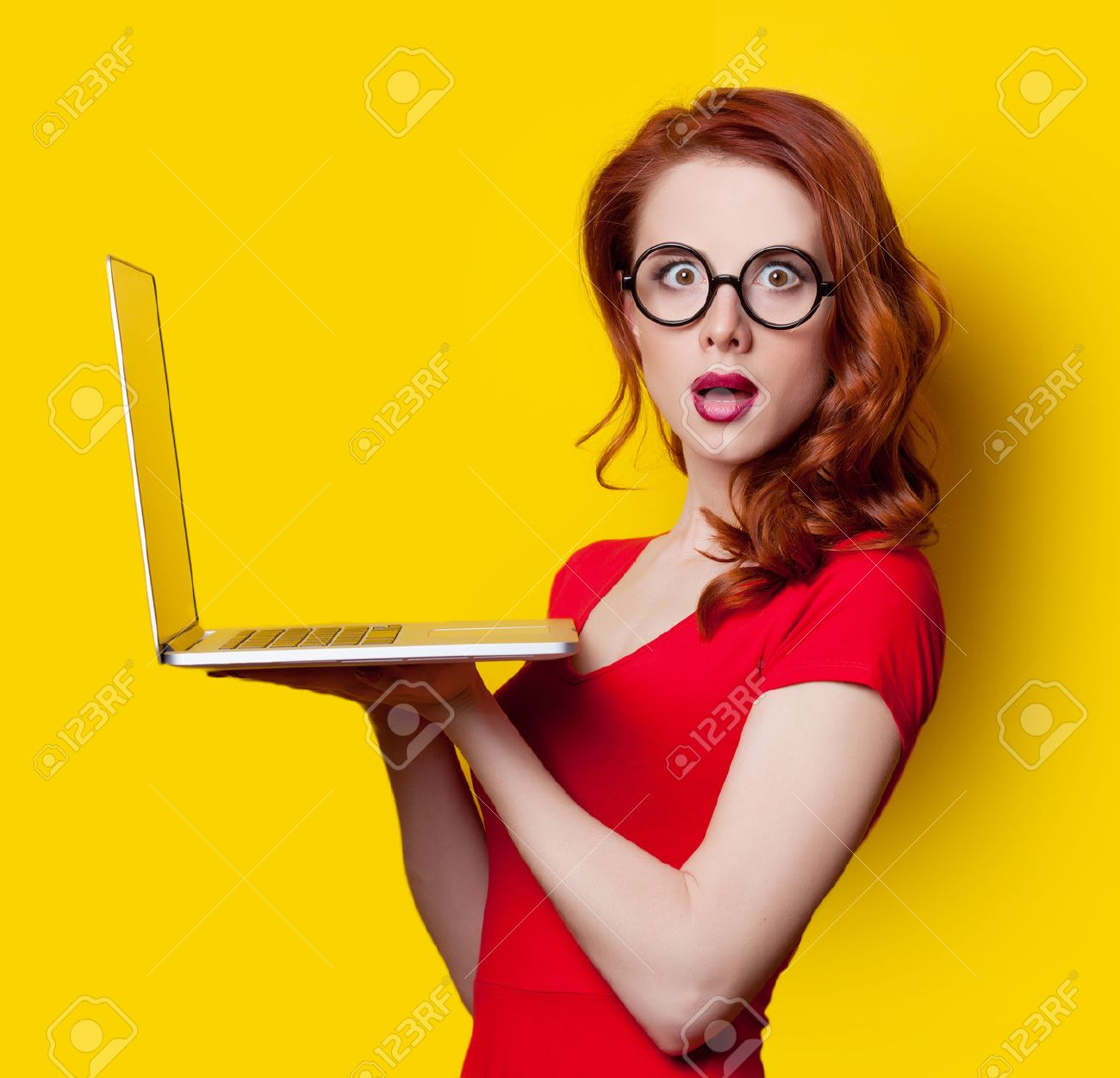 Surprised redhead girl with laptop computer in red dress on yellow background. - 40455024