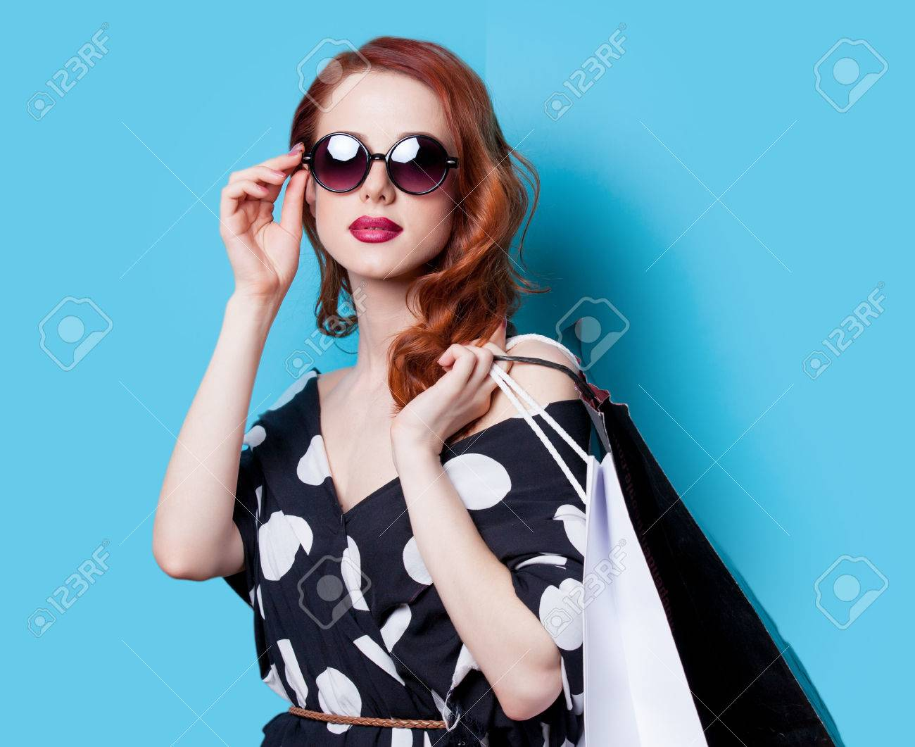 Redhead girl in black dress with shopping bags on blue background - 40358101