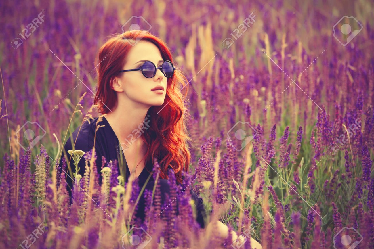 Portrait of a beautiful redhead girl with sunglasses on lavender field. - 41390922