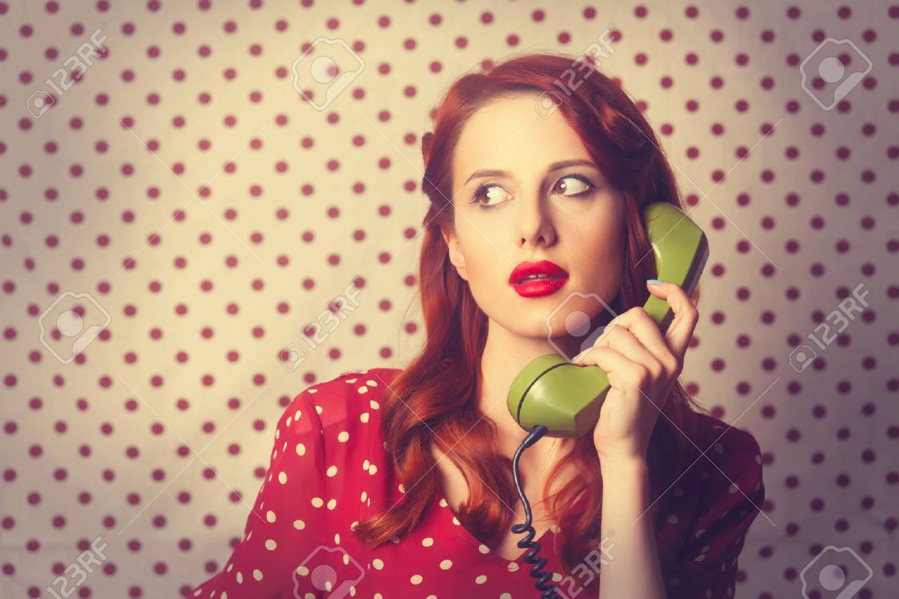 Portrait of a redhead girl with green dial phone on Polka dot background. - 41552151