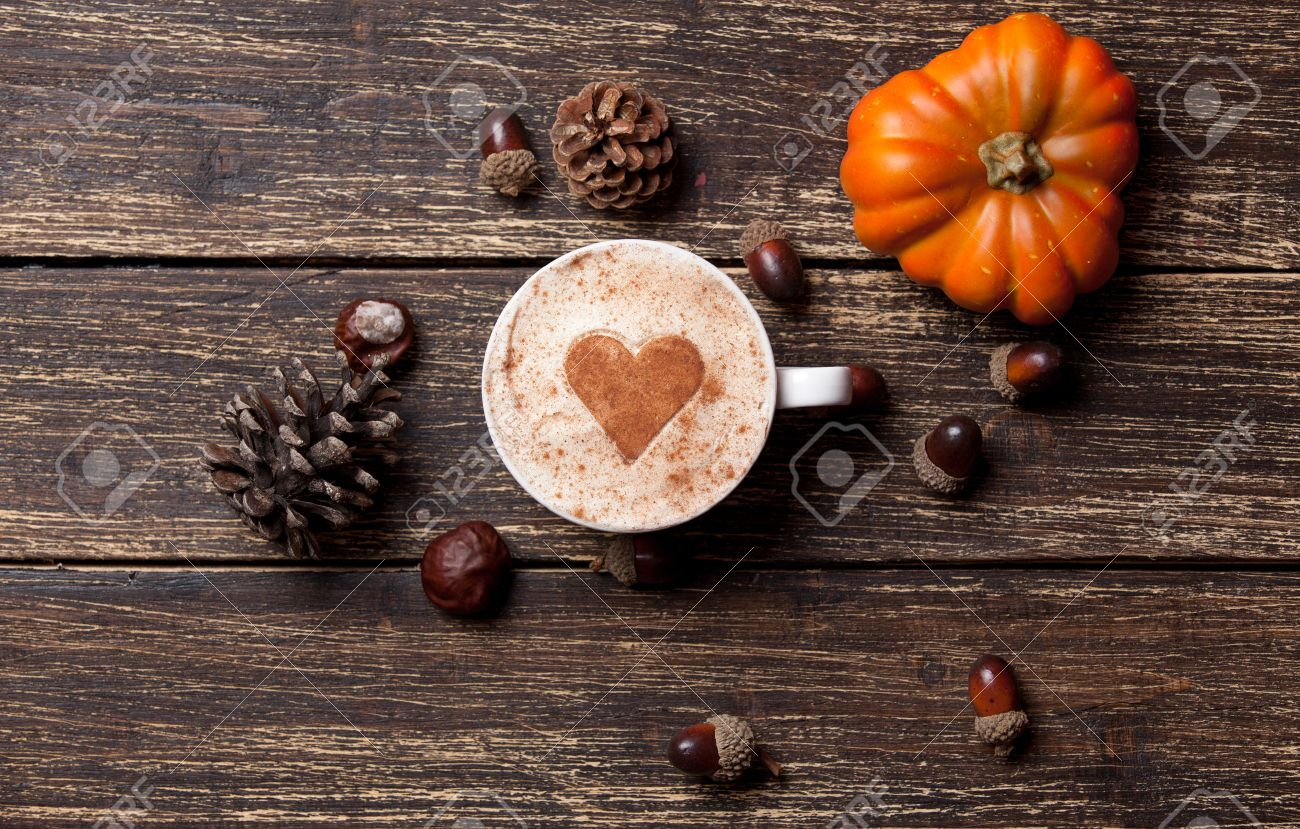 Cup of coffee with heart shape and pine cone with acorn and pumpkin on wooden background - 43008602