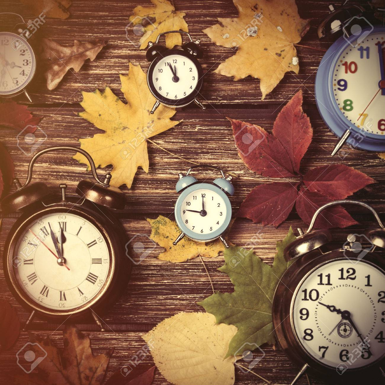 Autumn leafs and alarm clock on wooden table. - 43819153