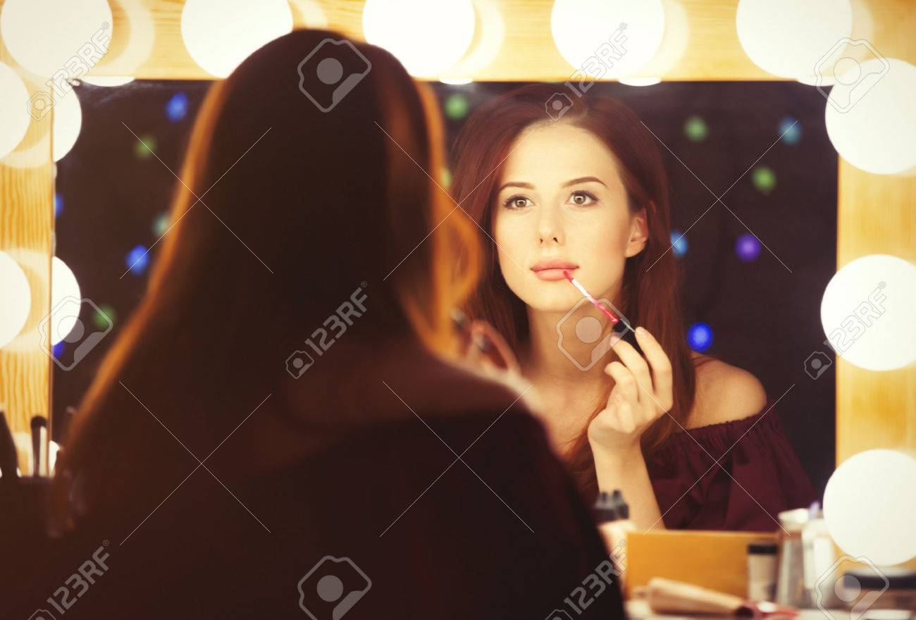 Portrait of a beautiful woman as applying makeup near a mirror. Photo in retro color style. - 43776375