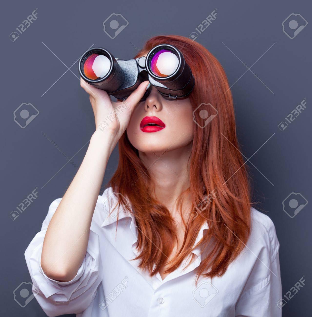 Portrait of a surprised businesswomen in white shirt with binocular on grey background. - 44029624