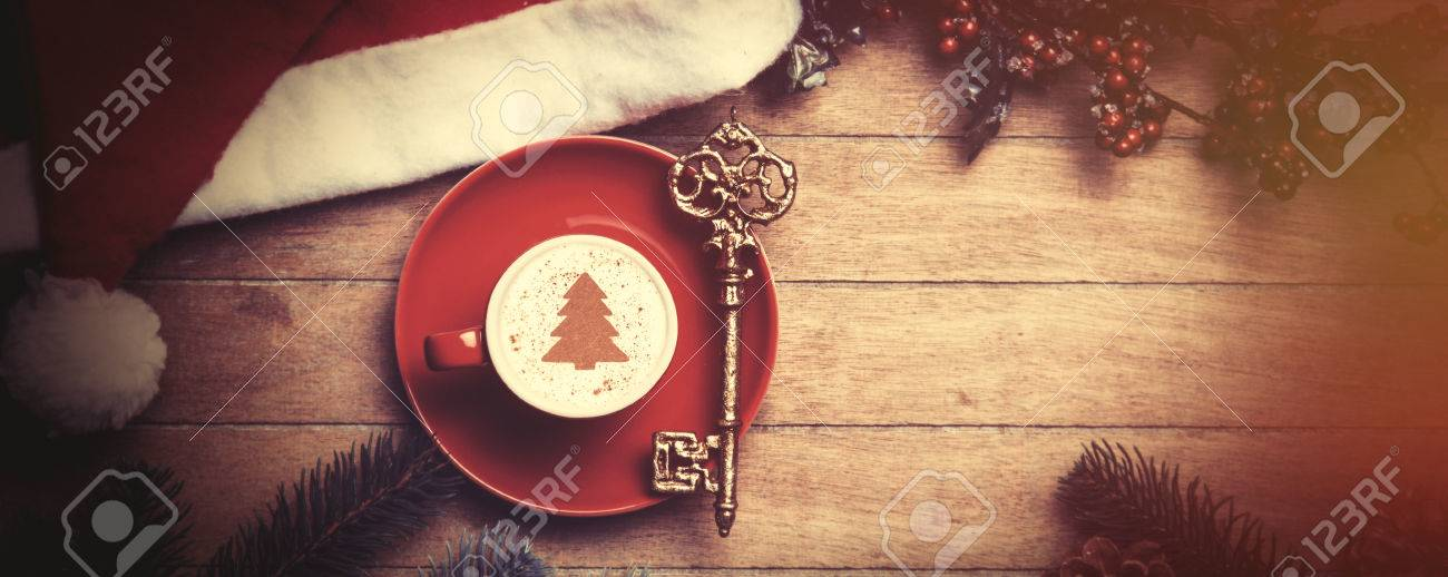 Cappuccino with key on wooden table. - 44352394