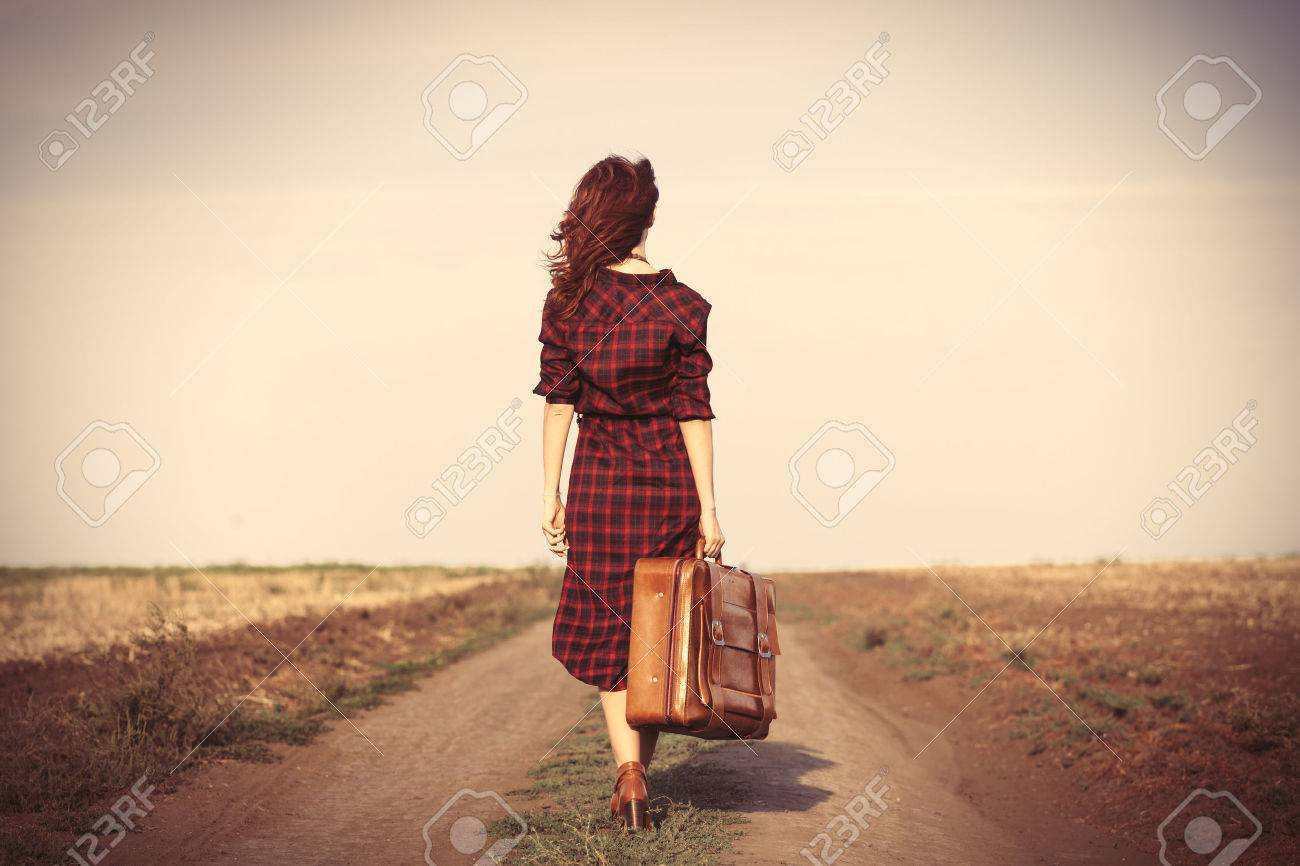 Beautiful girl in plaid dress with bag on countryside - 44352377