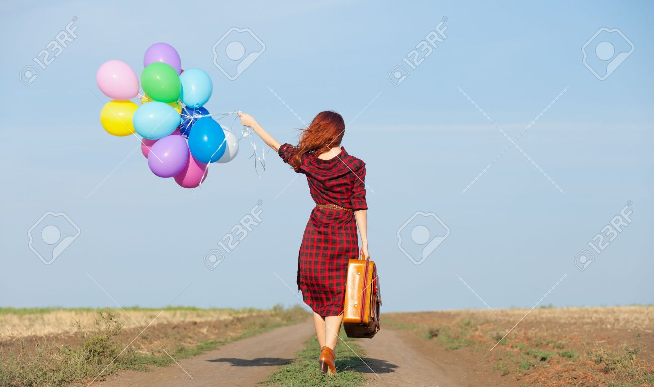 Beautiful girl in plaid dress with multicolored balloons and bag on countryside - 44352343