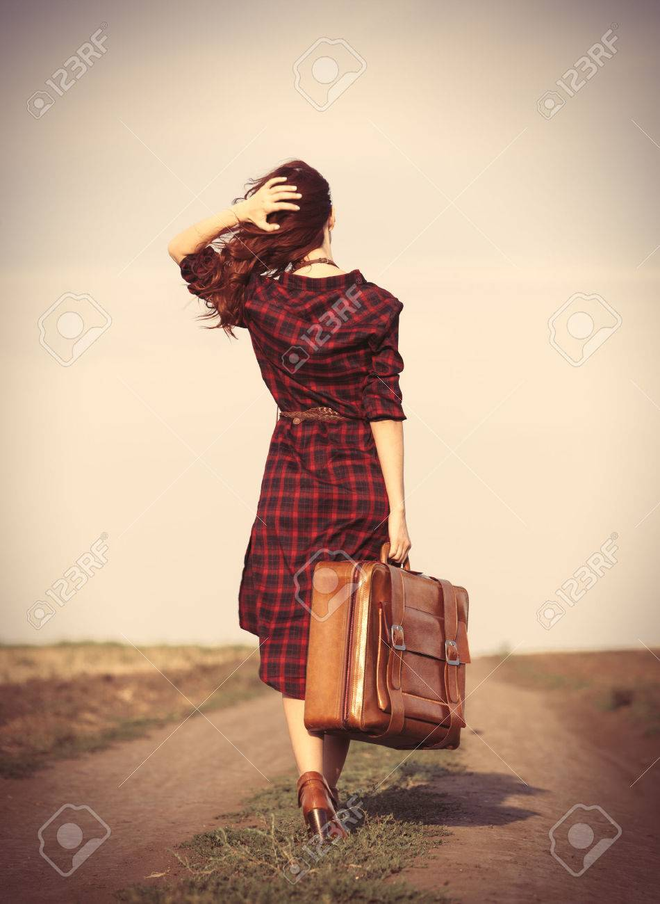 Beautiful girl in plaid dress with bag on countryside - 44351745
