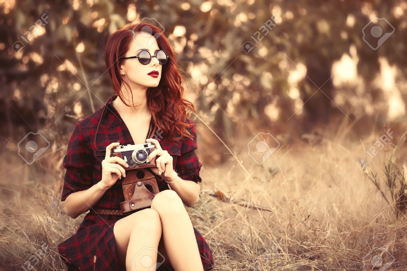 Beautiful girl in plaid dress retro camera and sunglasses at countryside - 44351768