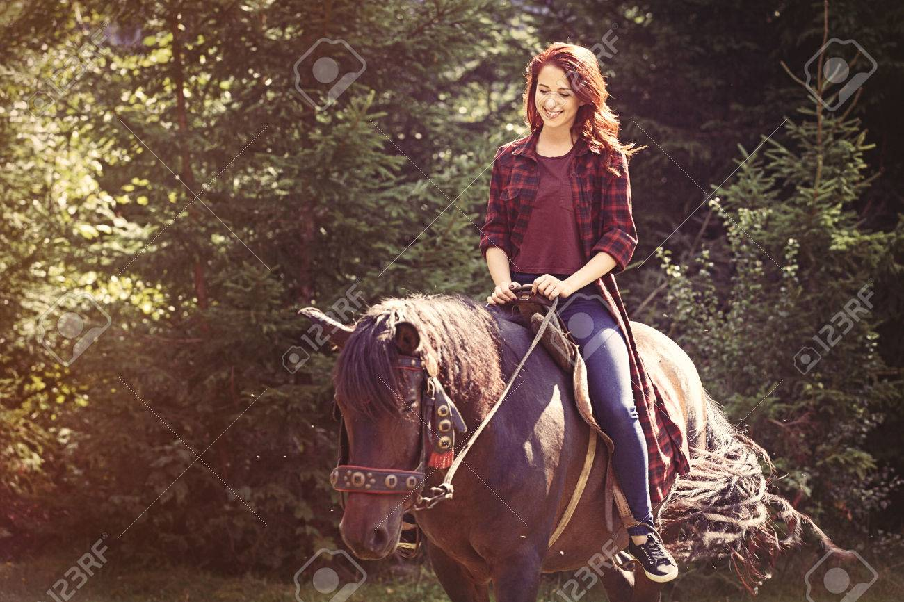 Redhead girl with horse in the forest - 45605010