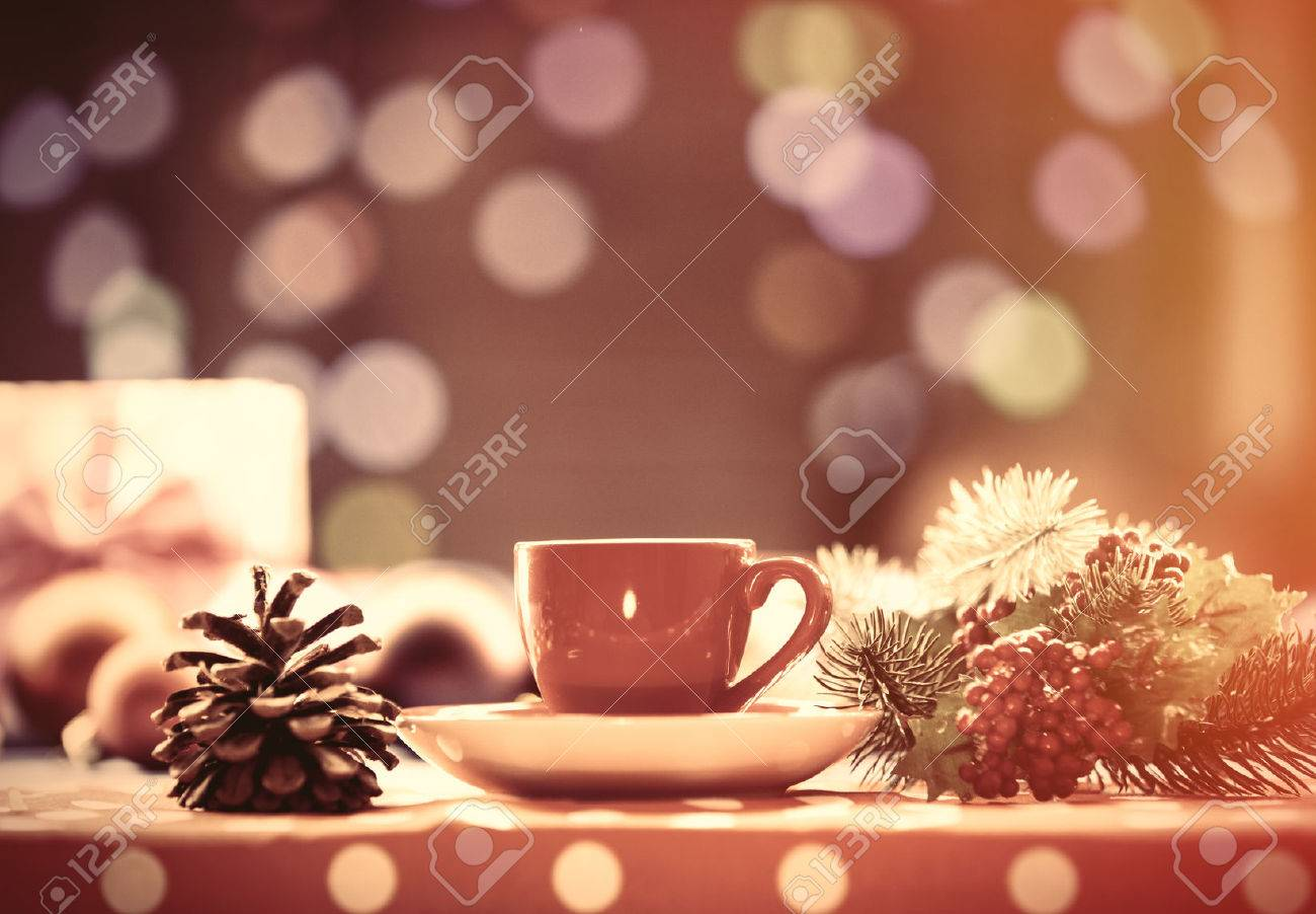 Cup of tea and branch with Christmas lights on background. - 45820998
