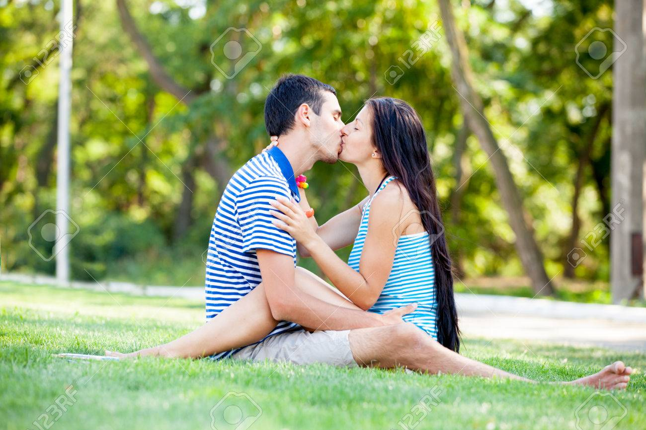 photo of cute couple sitting and kissing on the grass on the stock
