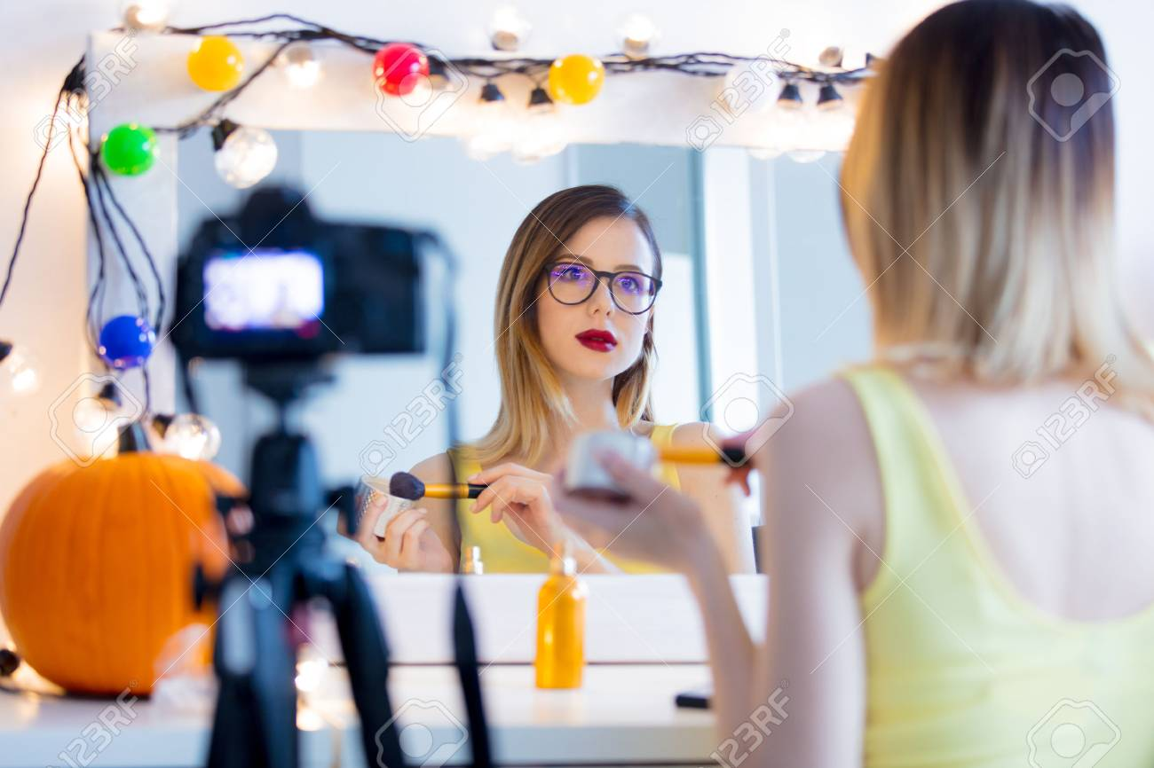 Young caucasian blogger woman applying cosmetics at camera for Video-sharing website. Home location near a mirror - 84863049