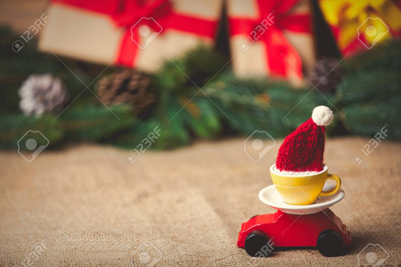 Red Toy Car And Cup Of Tea With Hat On Christmas Gifts Background ...