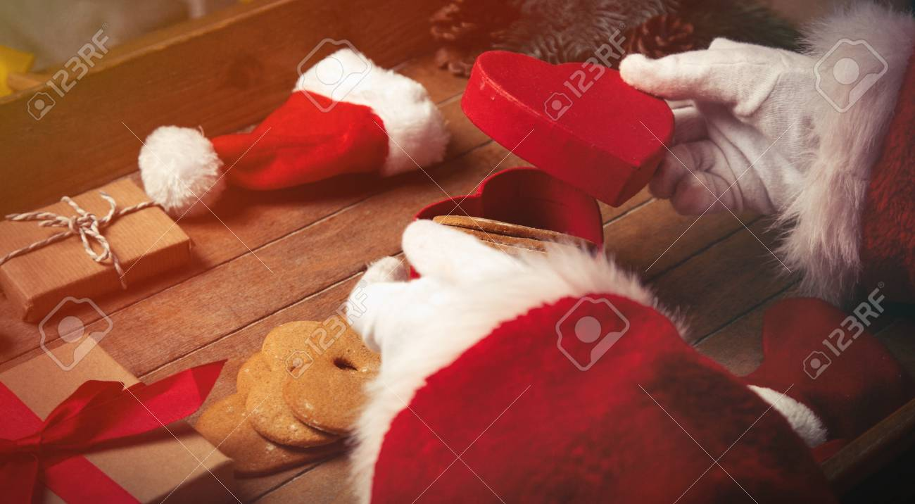 Santa Claus Wrapping Up Christmas Gifts And Cookies On Wooden