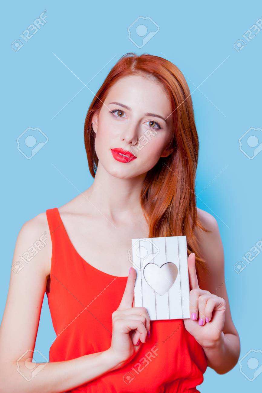 Redhead Girl In Coral Clothes With Photo Frame On Blue Background