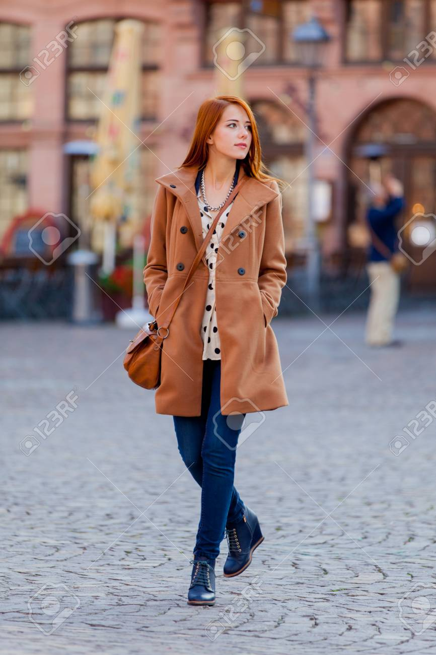 b0b4d9f91f8 Stock Photo - Young redhead woman in coat have a rest on Frankfurt streets,  Germany