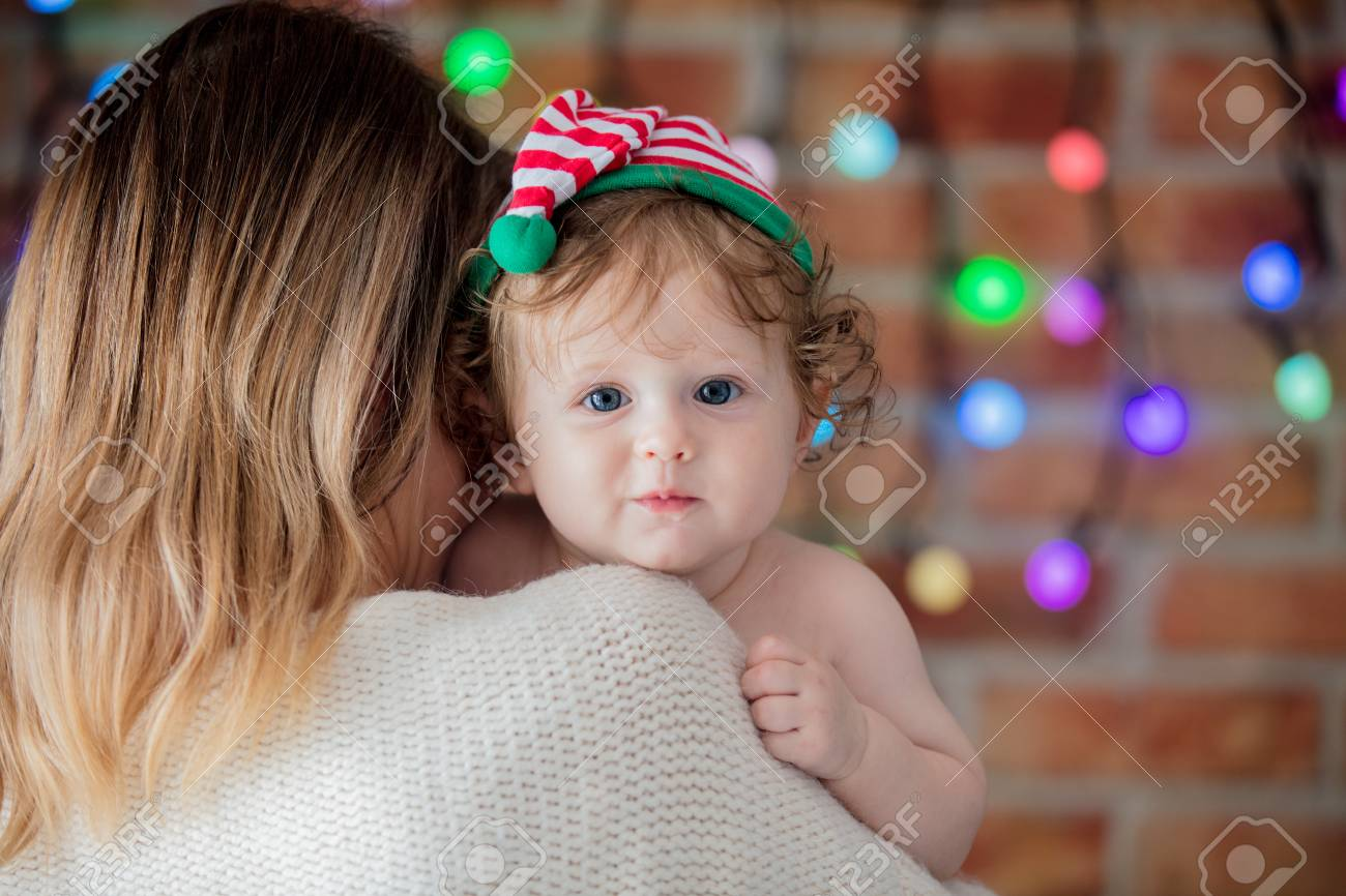 2048d1e5b2473 Beautiful little baby boy in elf hat and mother with fairy lights on  background. Christmas
