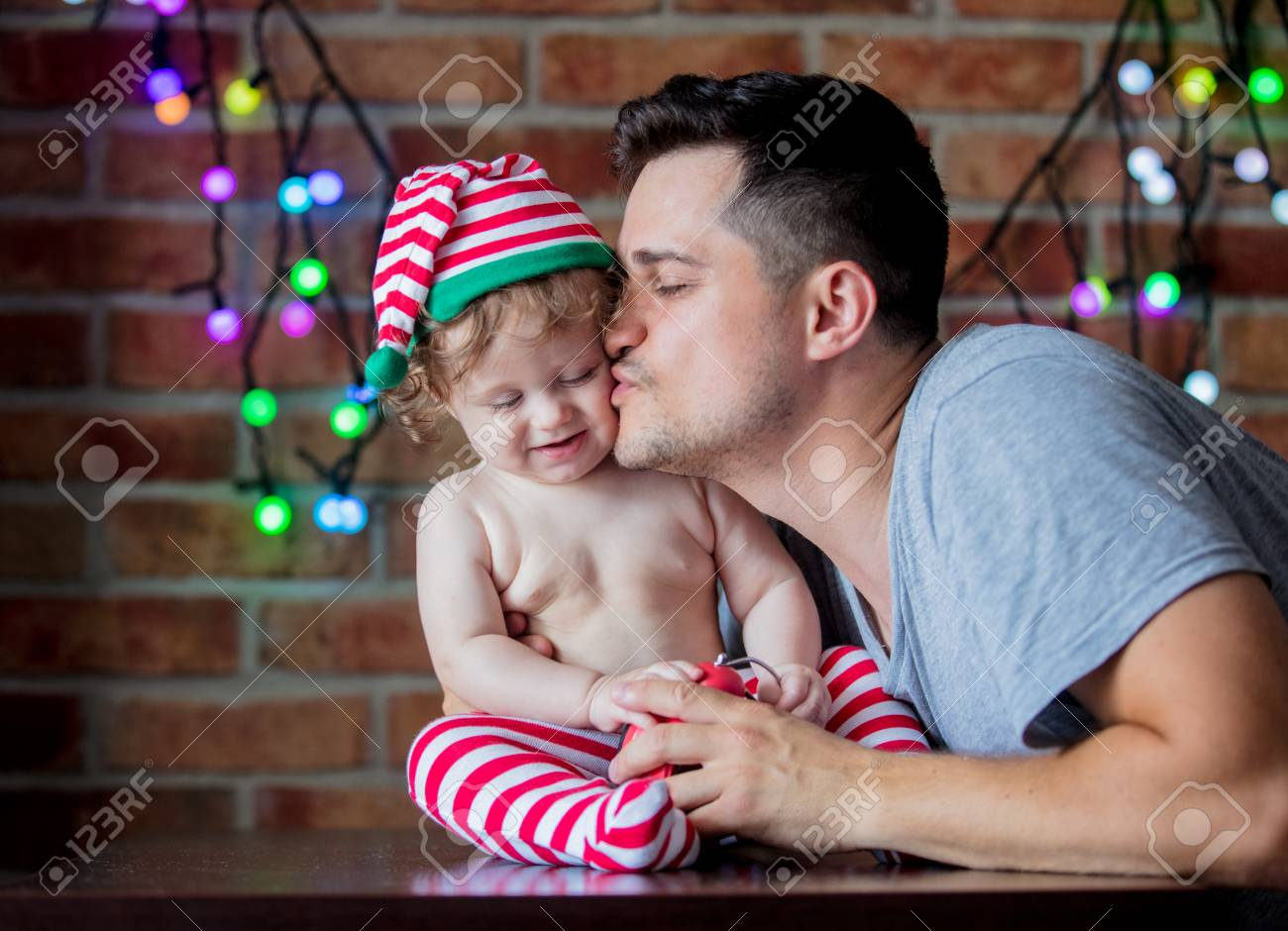 c9e1c879ef305 Beautiful little baby boy in elf hat and father with alarm clock and fairy  lights on