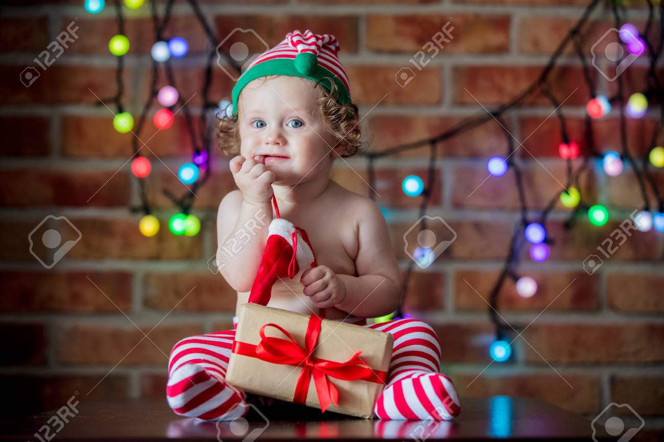 7e9f88acdf237 Beautiful little baby boy in elf hat with fairy lights on background. Christmas  time season