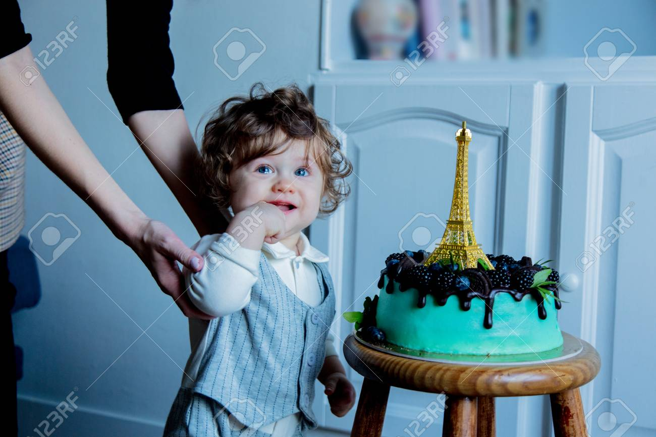 Little Toddler Boy With His First Cake On Birthday Is Cream And Eiffel