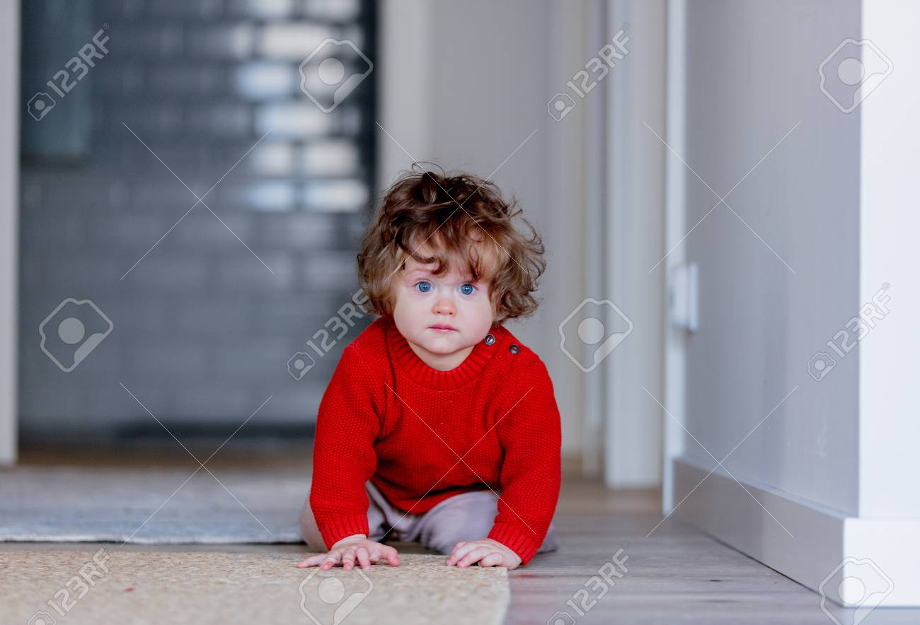 Little Toddler Boy On A Floor At Home Wearing In Red Sweater Stock